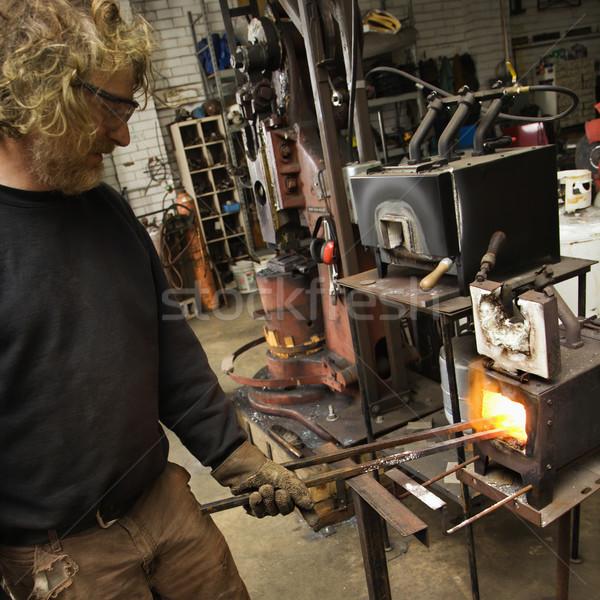 Metalsmith heating metal in forge. Stock photo © iofoto