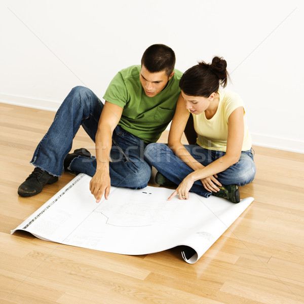 Couple reading blueprints. Stock photo © iofoto