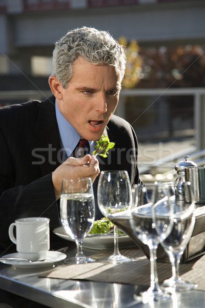 Businessman eating lunch. Stock photo © iofoto