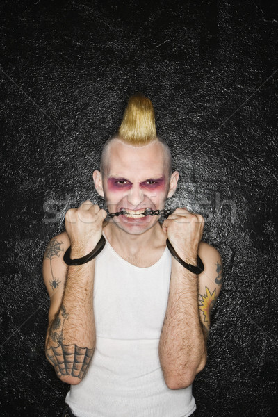 Punk biting handcuffs. Stock photo © iofoto