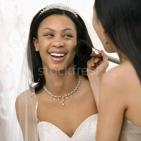 Bridesmaid applying makeup to bride. Stock photo © iofoto