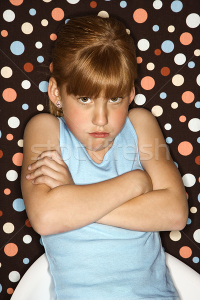 Girl pouting with arms crossed. Stock photo © iofoto