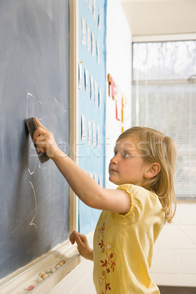 Girl Erasing Writing on Blackboard Stock photo © iofoto