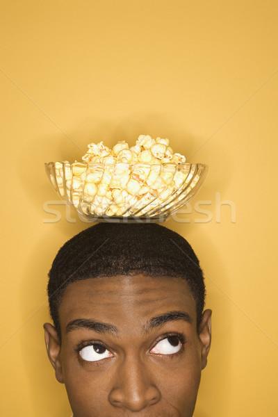 Man balancing voedsel jonge kom popcorn Stockfoto © iofoto
