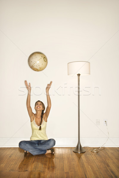 Attractive Young Woman Smiling and Sitting Tossing a Globe Stock photo © iofoto