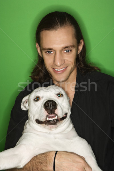 Man holding white dog on lap. Stock photo © iofoto