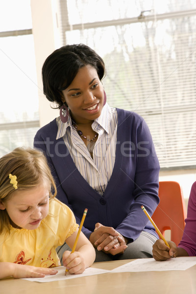 Teacher Smiling and Helping Students With Schoolwork  Stock photo © iofoto