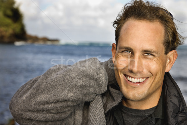 Man smiling by ocean. Stock photo © iofoto