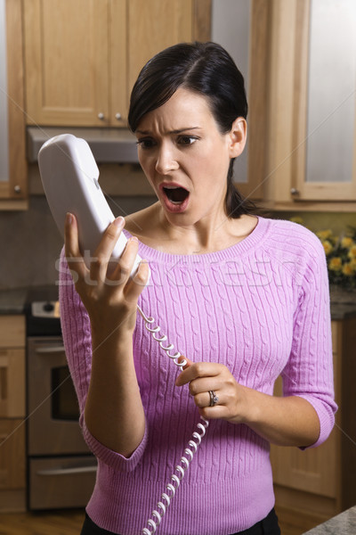 Woman Holding Phone in Disbelief Stock photo © iofoto