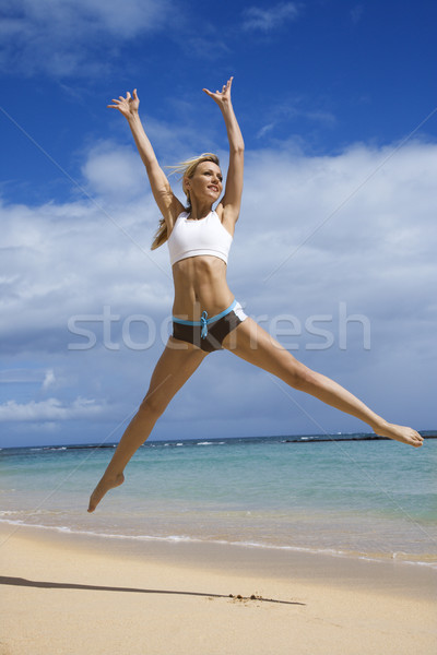 Stock photo: Woman jumping on beach.
