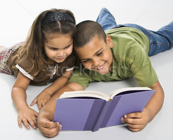 Brother and sister reading book together. Stock photo © iofoto