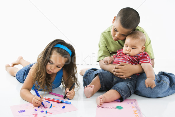 Hispanic girl coloring with brothers. Stock photo © iofoto