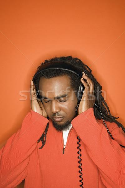 Stock foto: Mann · hören · Kopfhörer · tragen · orange · Kleidung