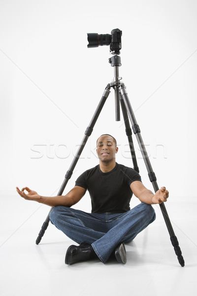 Photographer meditating under camera. Stock photo © iofoto