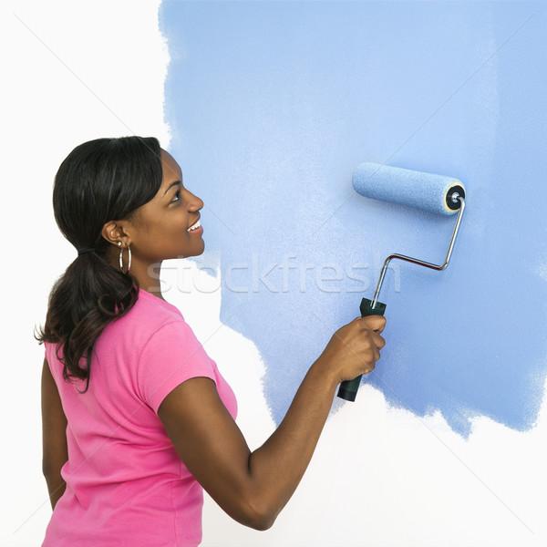 Pretty woman painting wall. Stock photo © iofoto