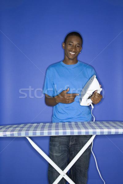 Teenage boy ironing. Stock photo © iofoto