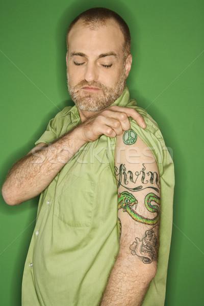 Kaukázusi férfi mutat tetoválás portré húz Stock fotó © iofoto