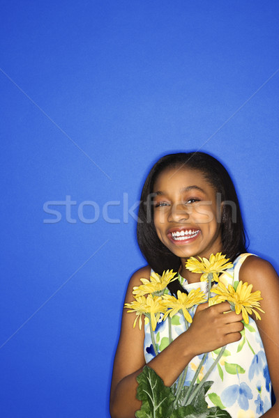 Girl smiling with flowers. Stock photo © iofoto