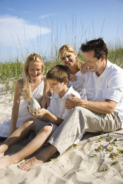 Family sitting on beach. Stock photo © iofoto