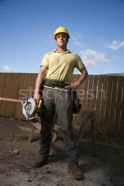 építőmunkás áll fűrész munkás munkavédelmi sisak biztonsági szemüveg Stock fotó © iofoto
