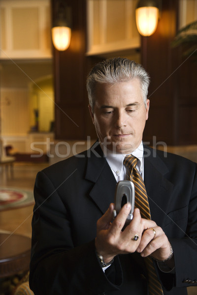 Businessman on cellphone in hotel. Stock photo © iofoto