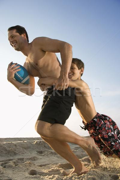 Son tackling dad playing football. Stock photo © iofoto