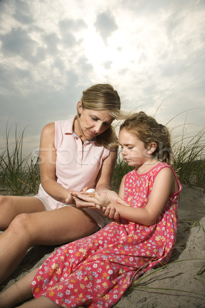 Anya lánygyermek néz kagylók ül homok Stock fotó © iofoto