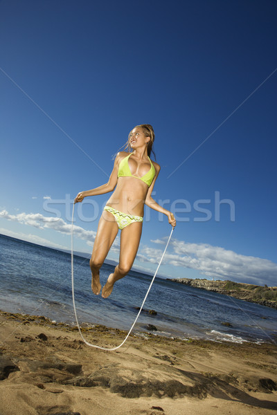 Woman jumping rope. Stock photo © iofoto