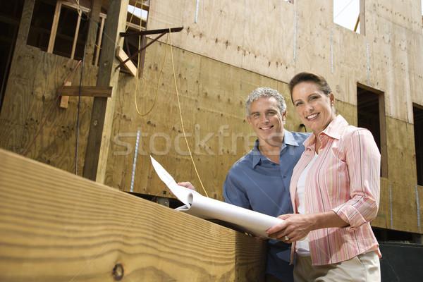 Man and woman reading blueprints. Stock photo © iofoto