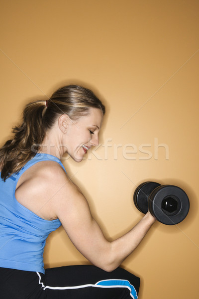 Woman lifting weights. Stock photo © iofoto