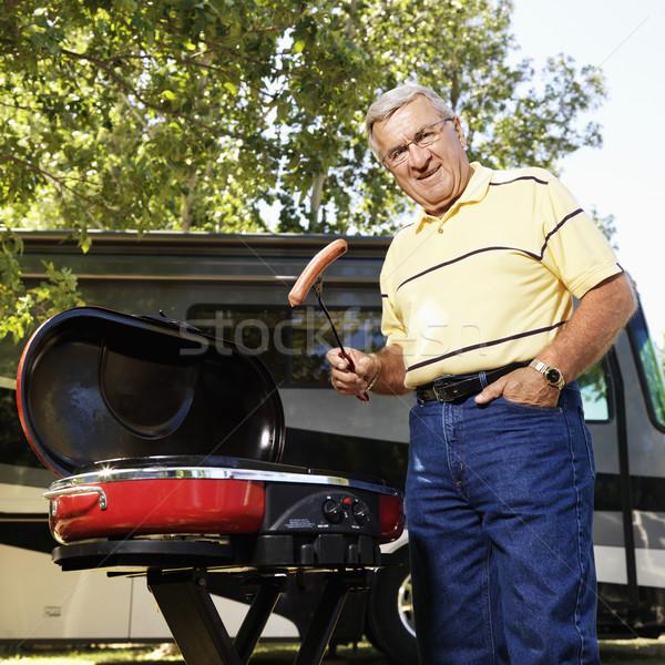 Senior man grilling by RV. Stock photo © iofoto