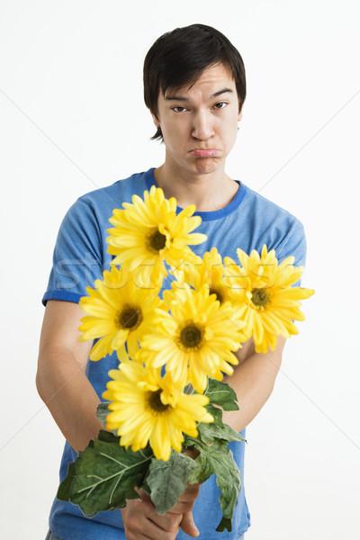 Pouting man holding bouquet. Stock photo © iofoto