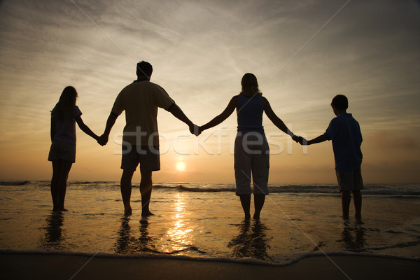 Family Holding Hands on Beach Watching the Sunset Stock photo © iofoto