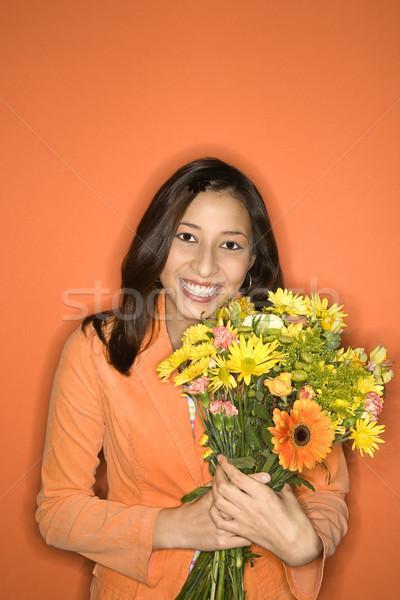 Girl smiling holding flowers. Stock photo © iofoto