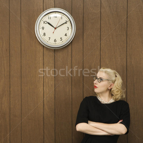 Woman looking at clock. Stock photo © iofoto