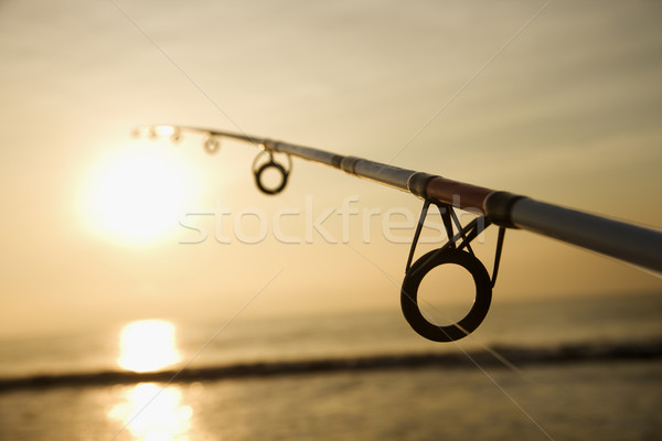 Stock photo: Fishing pole at sunset.