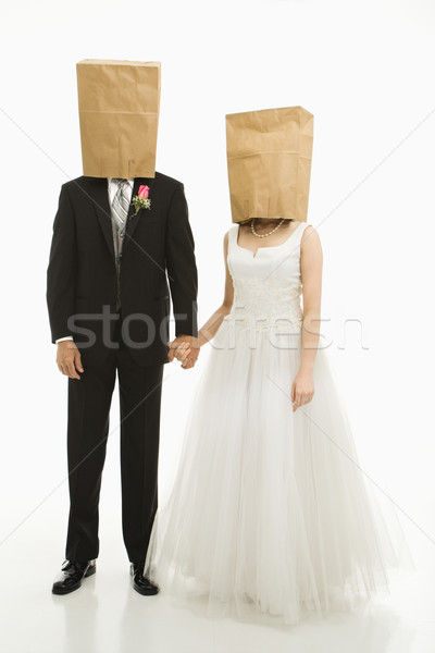 Stock photo: Wedding couple with bags over heads.