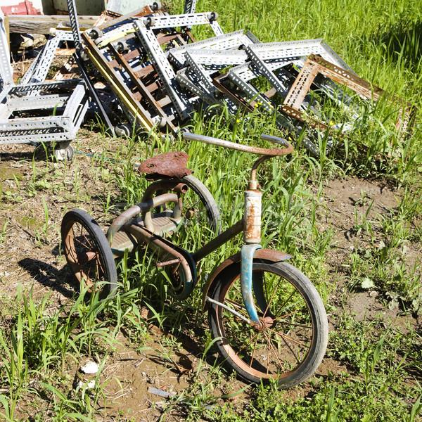 Terkedilmiş paslı üç tekerlekli bisiklet eski çimenli alan Stok fotoğraf © iofoto