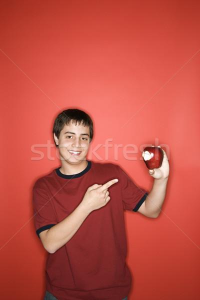 Teen boy pointing to apple.  Stock photo © iofoto