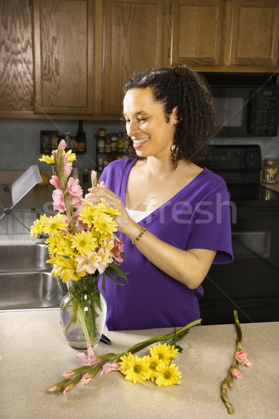 Pregnant woman arranging flowers. Stock photo © iofoto