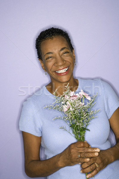 Smiling woman holding flowers. Stock photo © iofoto