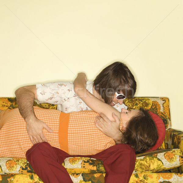 Couple kissing on sofa. Stock photo © iofoto