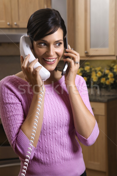 Woman Talking on Two Telephones Stock photo © iofoto