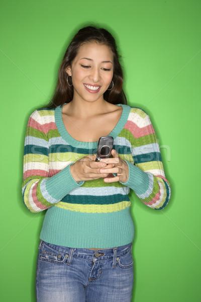Teen girl using cellphone. Stock photo © iofoto