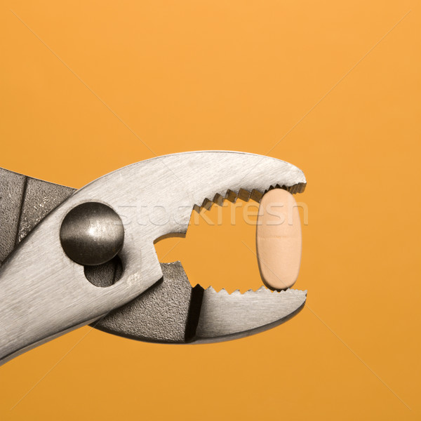 Pill Gripped With Pliers. Isolated Stock photo © iofoto