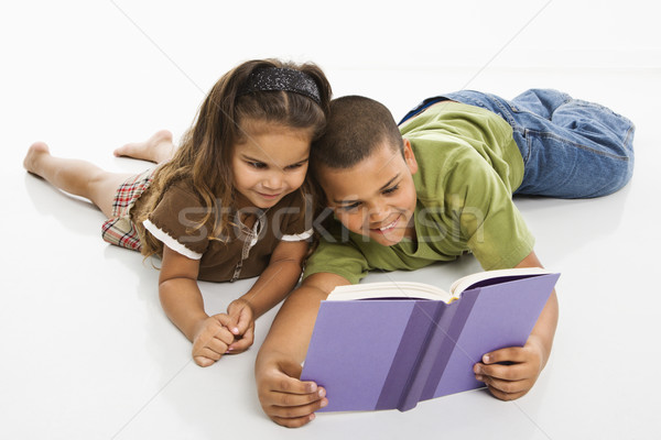 Boy and girl reading book together. Stock photo © iofoto
