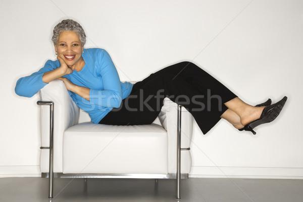 Woman lying back on chair. Stock photo © iofoto