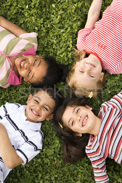 Children Lying in Clover With Heads Together Stock photo © iofoto