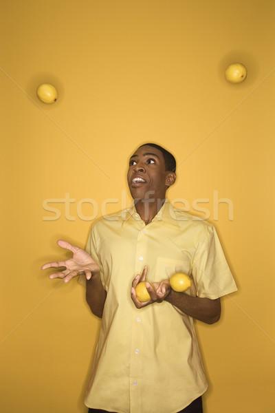 Man juggling lemons. Stock photo © iofoto