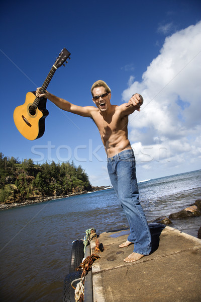 Enthusiastic Young Man With Guitar Standing Lakeside Stock photo © iofoto